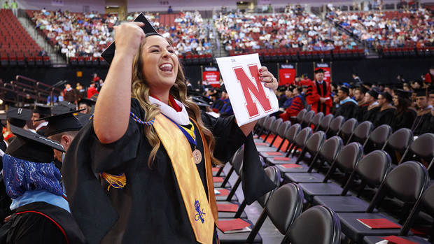 Alexandria Leavenworth gestures to her family and friends after receiving her master's degree in journalism and mass communications Friday at Pinnacle Bank Arena.