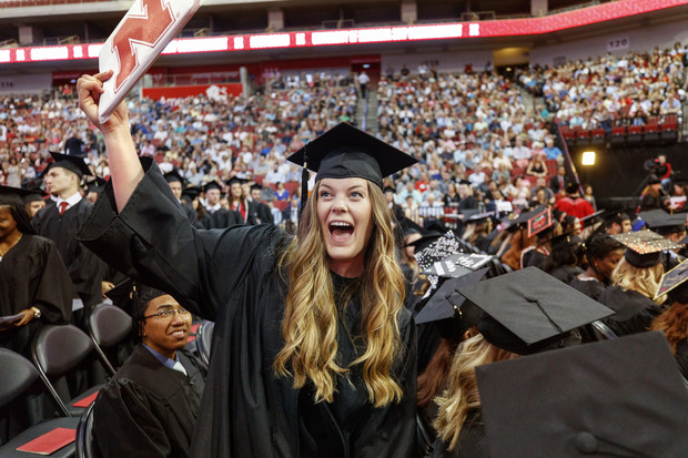 Anne Bachmann shows off her diploma to family and friends. She earned a Bachelor of Science in Business Administration.