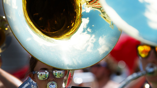 Band members are reflected in Kelsey Reeves' mirrored sunglasses as she plays her sousaphone during Cornhusker Marching Band practice Aug. 16 in Memorial Stadium.