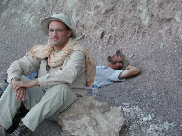 Matt Joeckel (front) and colleague, Gary Hunt, rest at the base of a Utah cliff face.