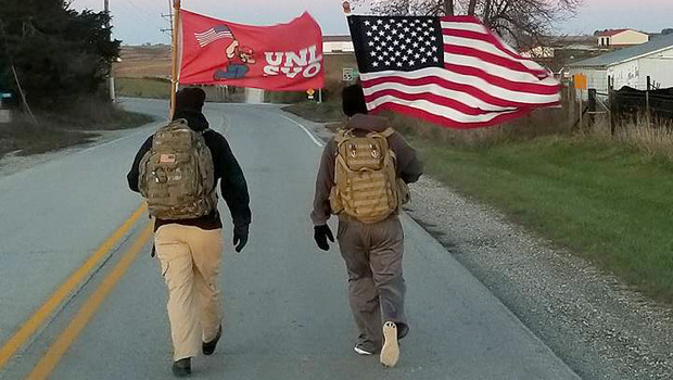 Members of the Nebraska Student Veteran Organization walk along an Iowa highway during the 2017 The Things They Carry Ruck March. The event, organized by Nebraska and Iowa students, is designed to raise public awareness of veteran suicides.