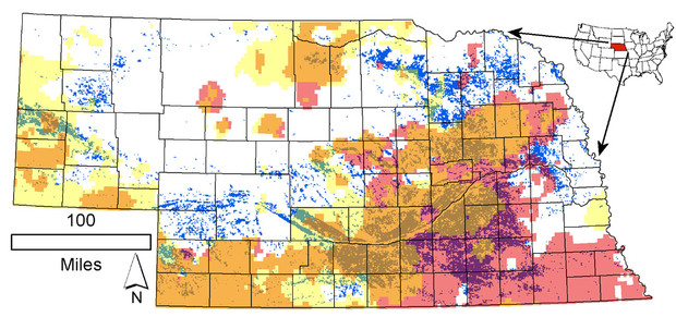 Distribution of the 1-square-kilometer cells where irrigated land in 2012 exceeded 50 percent of the cell area (blue-green dots) in Nebraska. Pink corresponds to declining annual, while yellow corresponds to declining irrigation-season (May-July) precipitation rates over the 1979-2015 period. The brownish color marks their spatial overlap.