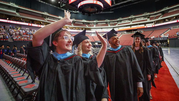 (From left) Maggie Fischer, Natalie Floreani and Phillip Foster wave to the crowd as they enter Pinnacle Bank Arena for the graduate and professional degrees ceremony May 4.