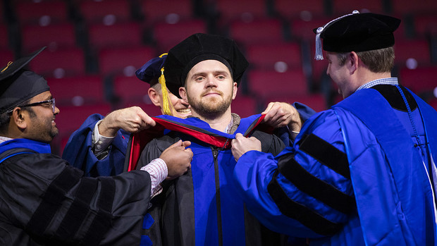 John Evans IV has his doctoral hood placed over his head by professors Santosh Pitla and Joe Luck during the graduate and professional degree ceremony Dec. 14 at Pinnacle Bank Arena. Evans earned a Doctor of Philosophy in biological engineering.