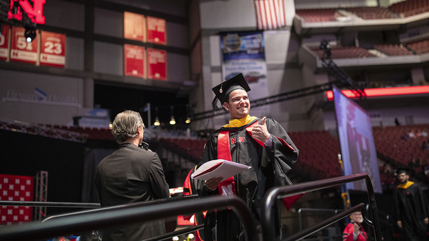 Tyler Moravec of Omaha gives his family and friends a thumbs-up after receiving his Master of Science in construction engineering and management May 3 during the graduate and professional degree ceremony at Pinnacle Bank Arena.