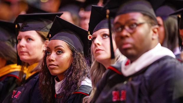 Briana Aldridge watches the greetings on the video screen at the start of the graduate and professional degree ceremony Dec. 20 at Pinnacle Bank Arena. Aldridge earned a Master of Arts.
