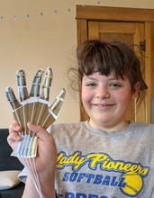 A youth shows the robot hand she created during Nebraska 4-H's Living Room Learning livestream March 17.