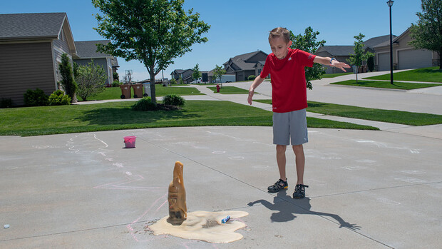 Evan Washburn watches the reaction after dropping a Mentos candy into a soda bottle in his family's driveway. The activity was part of the Virtual Vibes 4-H camp.