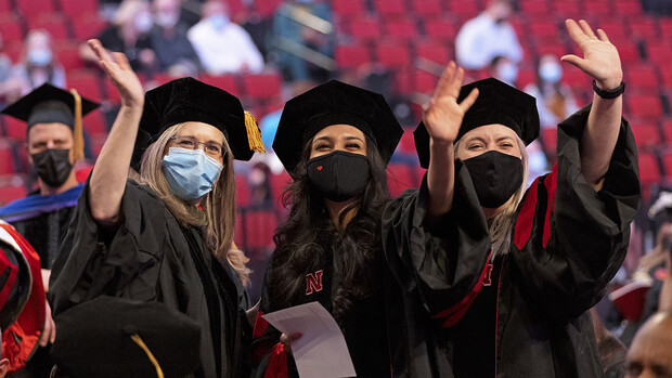 Stacie Ray (left), professor of practice in special education and communication disorders, and audiology doctoral students Manami Shah (center) and Emma Wilken wave to family and friends before the graduate and professional degree ceremony May 7 at Pinnacle Bank Arena.