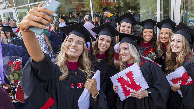 Speech-language pathology master's graduates gather for a selfie outside Pinnacle Bank Arena following the graduate and professional degree ceremony Aug. 13.