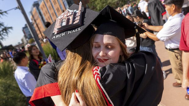 Leia Farrens and Margaret Gies, 2020 architecture graduates, hug after the undergraduate commencement ceremony Aug. 14 at Pinnacle Bank Arena. Gies decorated her mortar board with a rendering of Architecture Hall.