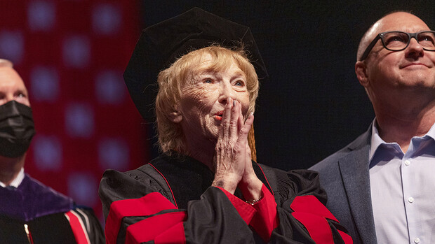 Leta Powell Drake, local television pioneer and Husker alumna, watches a video about her career on the scoreboard during the undergraduate commencement ceremony Aug. 14 at Pinnacle Bank Arena. The university presented Drake with an honorary Doctor of Humane Letters during the ceremony. Her son, Aaron (right), watches with her.
