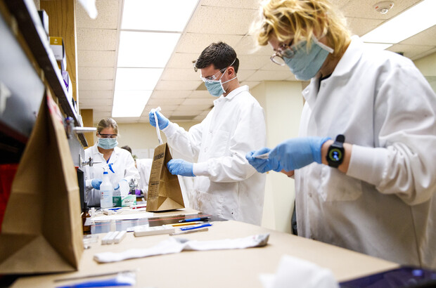 Brock Calamari removes a stained sock, which appears to be blood and will be tested. The work is part of the Forensic Science Capstone course, which brings together crime scene investigation, lab work and mock court testimony.