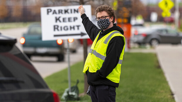 Noah Schwendeman directs traffic along Pinnacle Arena Drive as people arrive for their vaccine on April 7. Schwendeman said he volunteered for the clinic to help the community edge toward a return to normal.