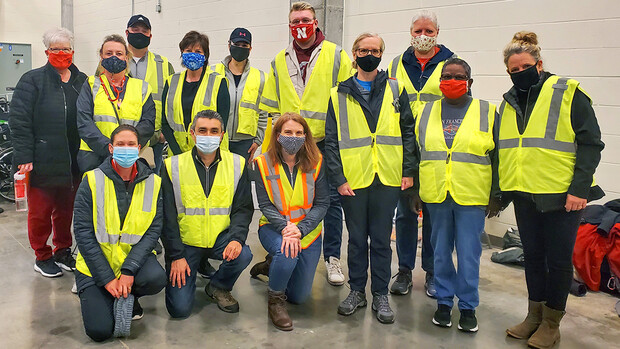 First-shift volunteers pose for a group photo following orientation on the morning of April 7. University teams filled two vaccine clinic shifts every day from April 7-9 at Pinnacle Bank Arena.