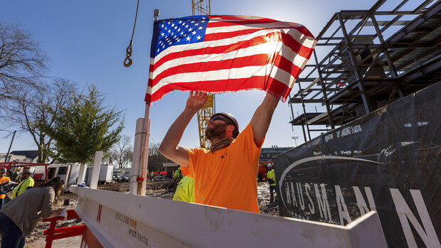 A Hausmann Construction employee unfurls a flag placed on the final steel beam during the topping out ceremony on April 9. The ceremony has roots to an ancient Scandinavian tradition that, in modern times, signals the completion of the internal structure of a building.