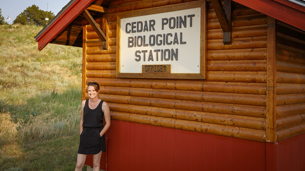 Sarah Kaizar stands next the cabin-like office at Cedar Point Biological Station.