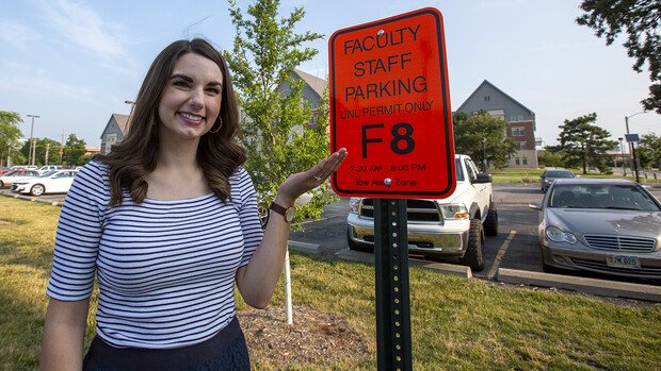Bonnie Martin stands next to her reserved parking sign near Nebraska Hall.