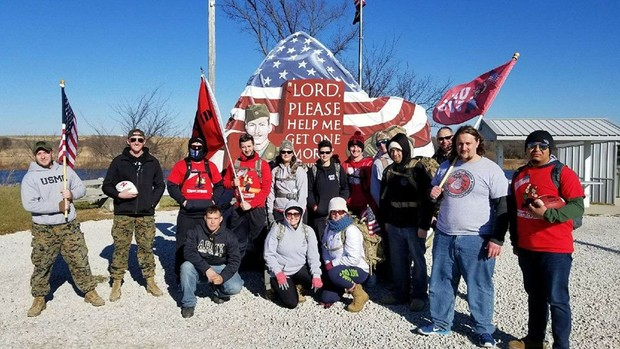 Huskers in the Nebraska Student Veteran Organization pose next to Freedom Rock in Menlo, Iowa, on Nov. 19. The Iowa team handed off the ceremonial football to the Nebraska team at the rock, which is painted each year to honor veterans' service.
