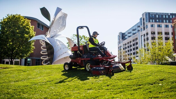 Worker mowing grass on campus