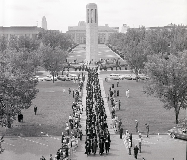 Nebraska graduates walk down the mall between Love Library and the Coliseum in this undated photo. Also pictured is Mueller Tower.
