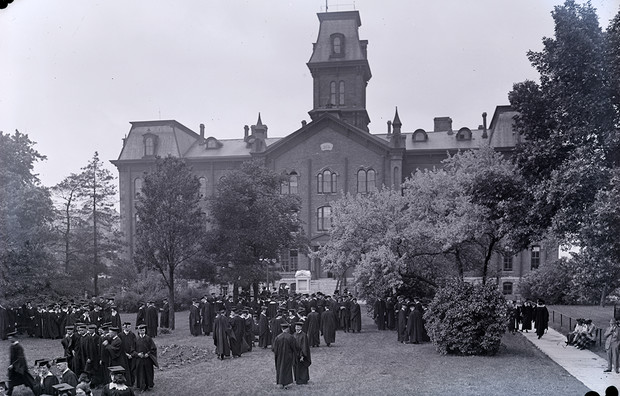 Graduates gather in front of University Hall, the first building on campus.
