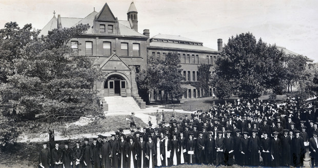Architecture Hall, shown here in an undated photo featuring graduates, is among the three original buildings still standing in NU's first four block plot. The other two buildings (not shown) are Brace Labs and Richards Hall.