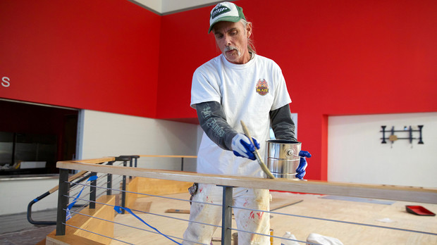 Mike Shore applies stain to wood on the warm viewing stand inside the John Breslow Ice Hockey Center.