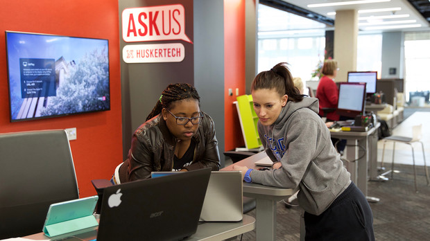 Jasmine Meeks (from left), a member of the Huskertech help desk team, assists Nicole Helm, a junior nutrition and health sciences major, in the new learning commons in Love Library on Nov. 11.