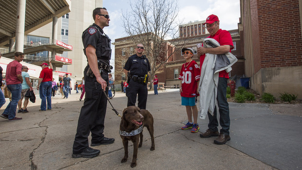 K-9 handler Greg Byelick (left) discusses his new partner, Justice, with Mike Heller (right) and his son Robbie prior to the start of the Huskers' spring football game on April 15. The University Police Department has added two K-9 patrols that will primarily be used for bomb detection.