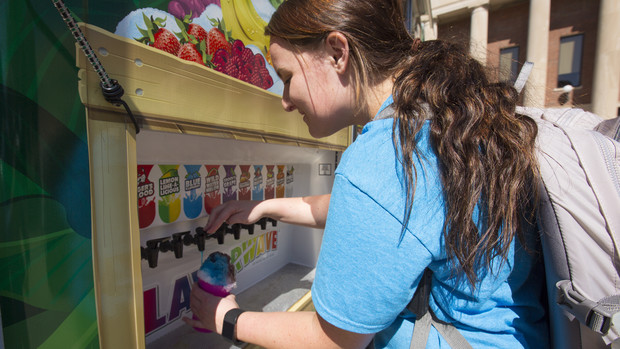Mallory Fangman, a junior nutrition and health sciences major, adds flavors to shaved ice purchased from the Kona Ice truck on Sept. 20.