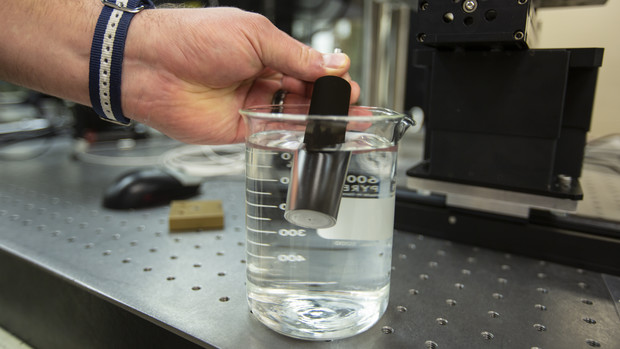 A metal sample modified to mimic shark skin repels water as it is placed in a beaker. The modified metal may some day be used to create submersibles that can travel more efficiently through water.