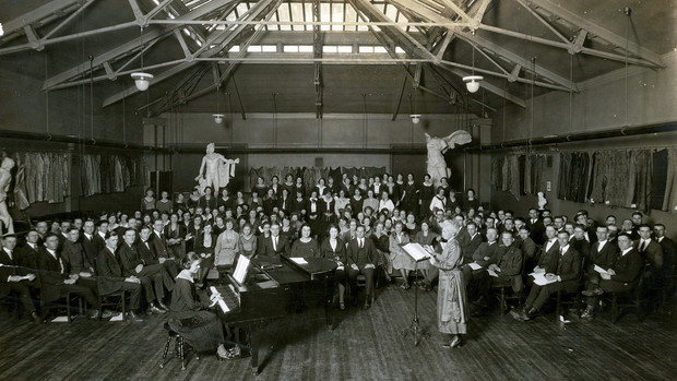 """Carrie Belle Raymond (standing, at right) directs the university chorus in April 1922 in what is today the Architecture Hall library reading room. Raymond was hired in 1894 to direct the university chorus and orchestra. She also taught music until her death in 1927. The first women's dormitory, Raymond Hall, was named for her in 1931. This image is included in Kay Logan-Peters' new book, """"University of Nebraska–Lincoln."""""""