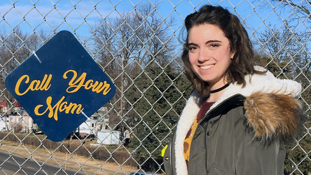 Anna Krause, a freshman history major, designed a sign that reminds people to call home. Students in the street art honors seminar posted their positive street art signs on fences throughout the Lincoln community on Dec. 5.