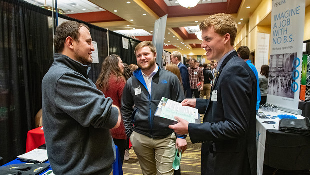 Jared Muhlbach and Carson Hicks talk with a recruiter from Farmers Cooperative at the STEM Career Fair in spring 2019.
