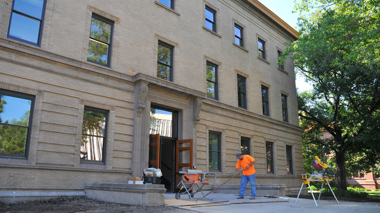 Quain VanArsdel cuts wood trim outside of UNL's  Brace Laboratory on Aug. 18.