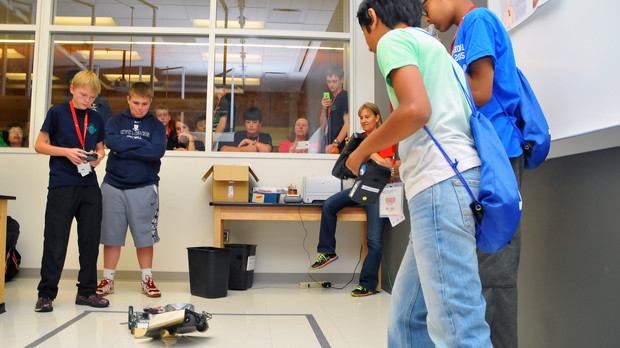 Sumo bot teams from (left) Oklahoma and Connecticut battle inside a Jorgensen Hall laboratory. The event is won by pushing an opposing robot out of the marked ring.