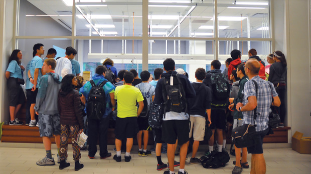 Students gather outside a Jorgensen Hall window to watch the Science Olympiad's sumo bots competition. The event pits robots designed by students against one another.