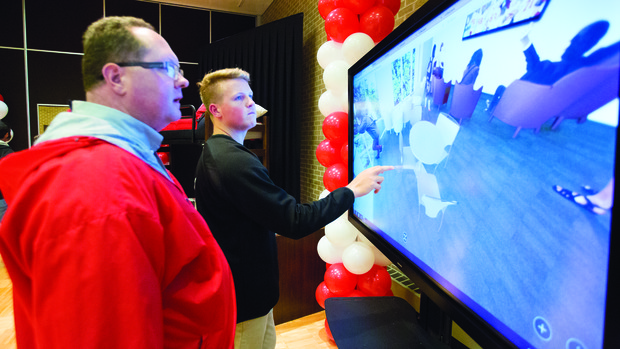 Todd (left) and Josh Seifert examine an interactive, 360-degree view of the university's new East Campus residence hall during a Nov. 17 open house at the East Union.
