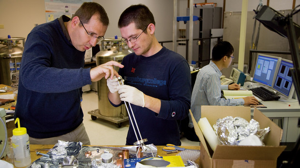Axel Enders, associate professor of physics and astronomy, works with a graduate student in a campus research lab.