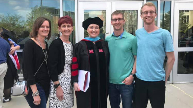 Nicole Frerichs (center) poses outside Pinnacle Bank Arena with family after receiving her doctoral degree in 2019.