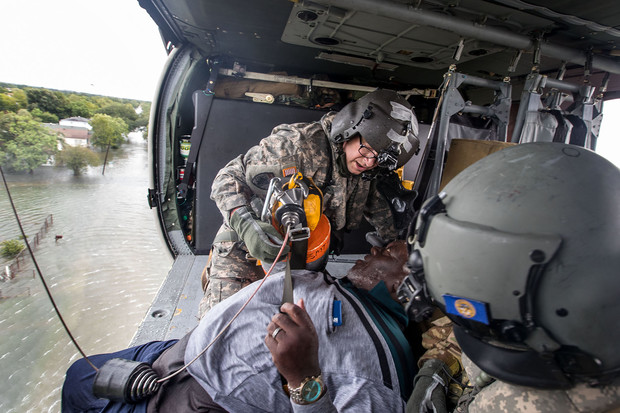 Nebraska National Guard members hoist a man rescued from flood waters in Port Arthur, Texas, into a helicopter. Ryan Green is a crew chief on a Blackhawk medevac helicopter and, among his tasks, is running the rescue hoist.