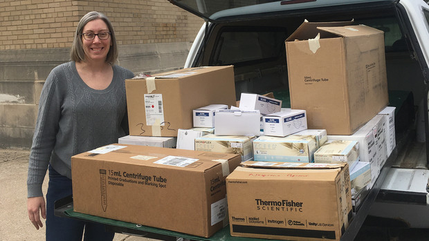 Rebecca Wachs, assistant professor of biological systems engineering, stands next to the medical supplies collected through a campus lab donation drive. The supplies were given to Bryan Health in Lincoln to assist with the response to COVID-19.