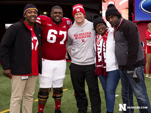 Charlie Foster poses for a photo with her husband and two sons and Coach Scott Frost