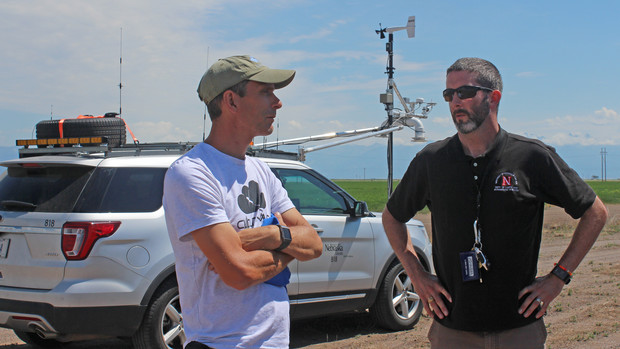 Nebraska's Adam Houston (right) talks with a colleague during a storm chase.