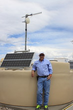 Gregory Snow stands beside a cosmic ray particle detector at the Pierre Auger Observatory in Argentina