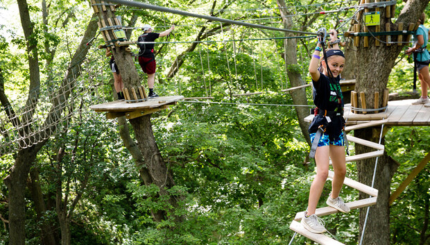 A young visitor completes the GoApe ropes course high in the trees at Mahoney State Park.