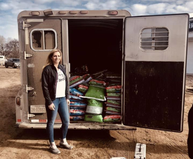 Katelyn Petersen stands next to a horse trailer loaded with items she collected for flood victims.