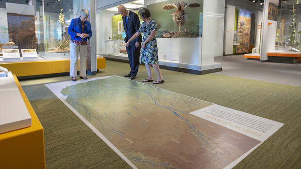 """Susan Weller (left) and Michelle Waite (right) discuss Nebraska's multiple rivers with Governor Pete Ricketts in the NU State Museum's """"Cherish Nebraska"""" exhibition."""