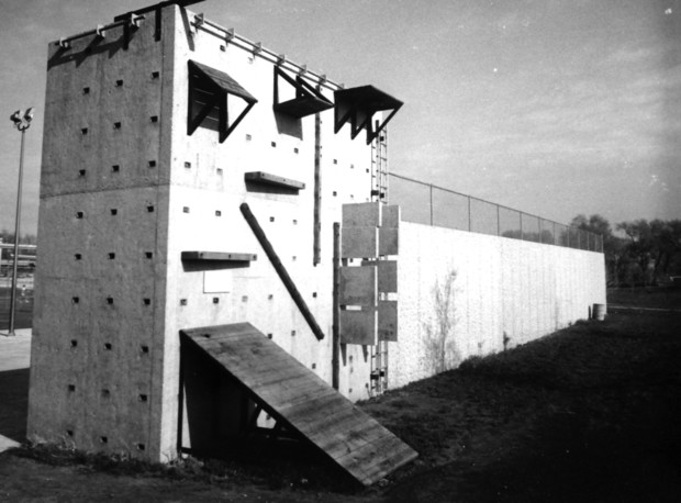 UNL's first climbing wall was built in 1976. The wall allowed for various climbing elements to be bolted onto it. The wall also served as a backstop to East Campus tennis courts.
